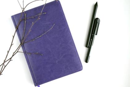 foto van paars schrift met pennen